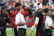 Offensive coordinator Mike McCoy (front), quarterbacks coach Byron Leftwich and head coach Steve Wilks talk with quarterback Josh Rosen #3 of the Arizona Cardinals during the second half against the Denver Broncos at State Farm Stadium on October 18, 2018 in Glendale, Arizona.