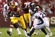 Running back Adrian Peterson #26 of the Washington Redskins rushes against the Denver Broncos in the first quarter during a preseason game at FedExField on August 24, 2018 in Landover, Maryland.