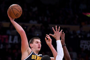 Nikola Jokic #15 of the Denver Nuggets passes out of a double team from Josh Hart #3 and Rajon Rondo #9 of the Los Angeles Lakers during a preseason game at Staples Center on October 2, 2018 in Los Angeles, California.