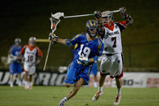 Kevin Drew #19 of the Charlotte Hounds keeps the ball away from Matt Bocklet #7 of the Denver Outlaws during their game at American Legion Memorial Stadium on June 27, 2015 in Charlotte, North Carolina.