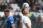 Cris Martin of Derby County heads the ball away from Darren McGregor during the pre season friendly match between Derby County and Rangers at iPro Stadium on August 2, 2014 in Derby, England.