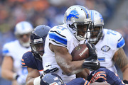 Reggie Bush #21 of the Detroit Lions is tackled by Demontre Hurst #30 of the Chicago Bears, Ryan Mundy #21 (right) and Jon Bostic #57 (behind) during the second quarter at Soldier Field on December 21, 2014 in Chicago, Illinois.