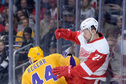 Tomas Tatar #21 of the Detroit Red Wings is checked into the boards by Robyn Regehr #44 of the Los Angeles Kings during the first period at Staples Center on February 24, 2015 in Los Angeles, California.