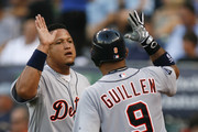Miguel Cabrera #24 of the Detroit Tigers is congratulated by Carlos Guillen #9 after scoring on a Victor Martinez single in the third inning at Kauffman Stadium on August 6, 2011 in Kansas City, Missouri.