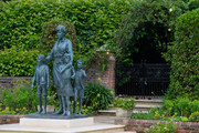 """The statue of Diana, Princess of Wales, by artist Ian Rank-Broadley, in the Sunken Garden at Kensington Palace. The bronze statue depicts the princess surrounded by three children to represent the """"universality and generational impact"""" of her work. Her short cropped hair, style of dress and portrait are based on the final period of her life. Beneath the statue is a plinth engraved with her name and the date of the unveiling, and in front is a paving stone engraved with an extract inspired by The Measure of A Man poem on July 1, 2021 in London, England. Today would have been the 60th birthday of Princess Diana, who died in 1997. At a ceremony here today, her sons Prince William, Duke of Cambridge and Prince Harry, Duke of Sussex unveiled a statue in her memory."""
