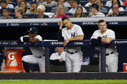 Andrew McCutchen #26, Giancarlo Stanton #27 and Luke Voit #45 of the New York Yankees looks on from the dugout against the Boston Red Sox in Game Four of the American League Division Series at Yankee Stadium on October 09, 2018 in the Bronx borough of New York City.