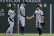 (L-R) Andrew McCutchen #26, Aaron Judge #99 and Brett Gardner #11 of the New York Yankees celebrate after their 6-2 win in Game Two of the American League Division Series against the Boston Red Sox at Fenway Park on October 6, 2018 in Boston, Massachusetts. The Yankees defeated the Red Boston Red Sox 6-2.