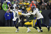 Russell Wilson #3 of the Seattle Seahawks releases the ball just before getting hit by the Green Bay Packers in the NFC Divisional Playoff game at Lambeau Field on January 12, 2020 in Green Bay, Wisconsin.
