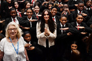 Alternative crop of image #1205706931) Meghan, Duchess of Sussex poses with school children making the 'Equality' sign following a school assembly during a visit to Robert Clack School in Dagenham to attend a special assembly ahead of International Women's Day (IWD) held on Sunday 8th March, on March 6, 2020 in London, England.