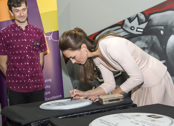 Nick O'Connor watches Catherine, Duchess of Cambridge as she signs a drum skin during their visit to the youth community centre, The Northern Sound System, in Elizabeth on April 23, 2014 in Adelaide, Australia. The Duke and Duchess of Cambridge are on a three-week tour of Australia and New Zealand, the first official trip overseas with their son, Prince George of Cambridge.