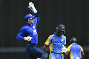 John Simpson (L) of South takes a return catch during the ECB North v South Series warm up game between South and Barbados XI at Kensington Oval on March 15, 2018 in Bridgetown, Barbados.