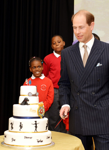 Prince Edward, Earl of Wessex prepares to cut a 50th birthday cake presented to him during an official visit on the Earl's 50th Birthday to Robert Browning Primary School in Walworth to see the work of youth charity Kidscape, recipients of grants from the Wessex Youth Trust, on March 10, 2014 in London, United Kingdom.