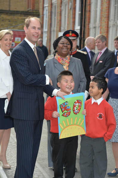 Prince Edward, Earl of Wessex watched by his wife the Countess of Wessex, is presented with a 50th birthday card by pupils John Lieu (L), nine, and Pharez Billy, seven, during an official visit on the Earl's 50th Birthday to Robert Browning Primary School in Walworth to see the work of youth charity Kidscape, recipients of grants from the Wessex Youth Trust, on March 10, 2014 in London, United Kingdom.