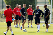 Glen Johnson, Wayne Rooney and Steven Gerrard share a joke with Gary Neville as puts out the cones during an England Training Session at London Colney on May 29, 2012 in London, England.