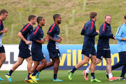 Wayne Rooney of England leads Steven Gerrard, Glen Johnson and Theo Walcott in a warm up during a training session at St Georges Park on August 12, 2013 in Burton-upon-Trent, England.