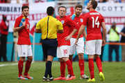 Wayne Rooney of England (C) speaks to referee Ricardo Salazar as Adam Lallana (L), Steven Gerrard (2nd R) and Jordan Henderson (R) look on as Salazar delays the match due to inclement weather in the first half during the International Friendly match between England and Honduras at Sun Life Stadium on June 7, 2014 in Miami Gardens, Florida.