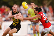 Kamdyn McIntosh of the Tigers handpasses the ball under pressure from Jake Long of the Bombers during the JLT Community Series AFL match between the Essendon Bombers and the Richmond Tigers at Norm Minns Oval on February 24, 2018 in Wangaratta, Australia.