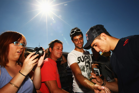 Sebastien Buemi of Switzerland and Scuderia Toro Rosso signs autographs for fans during previews to the European Formula One Grand Prix at the Valencia Street Circuit on July 24, 2010, in Valencia, Spain.
