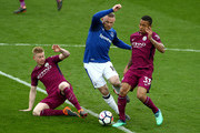 Wayne Rooney of Everton is challenged by Kevin De Bruyne of Manchester City and Gabriel Jesus of Manchester City during the Premier League match between Everton and Manchester City at Goodison Park on March 31, 2018 in Liverpool, England.