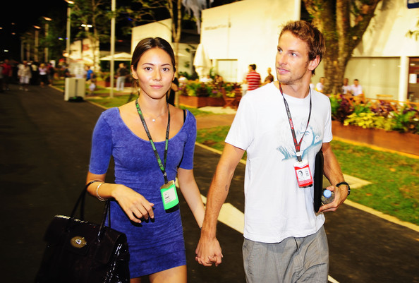 Jenson Button of Great Britain and Brawn GP and his girlfriend Jessica Michibata walk in the paddock during previews to the Singapore Formula One Grand Prix at the Marina Bay Street Circuit on September 24, 2009 in Singapore.