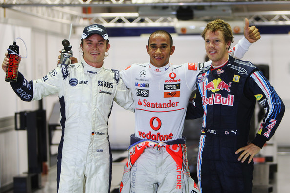 Pole sitter Lewis Hamilton (C) of Great Britain and McLaren Mercedes celebrates with second placed Sebastian Vettel (R) of Germany and Red Bull Racing and third placed Nico Rosberg (L) of Germany and Williams in parc ferme after finishing first during qualifying for the Singapore Formula One Grand Prix at the Marina Bay Street Circuit on September 26, 2009 in Singapore.
