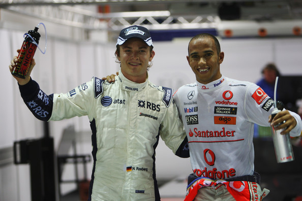 Pole sitter Lewis Hamilton (R) of Great Britain and McLaren Mercedes celebrates with third placed Nico Rosberg (L) of Germany and Williams in parc ferme after finishing first during qualifying for the Singapore Formula One Grand Prix at the Marina Bay Street Circuit on September 26, 2009 in Singapore.