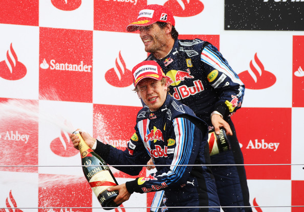 Sebastian Vettel (front) of Germany and Red Bull Racing celebrates with second placed Mark Webber (rear) of Australia and Red Bull Racing on the podium after winning the British Formula One Grand Prix at Silverstone on June 21, 2009 in Northampton, England.