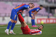 Koke of Atletico de Madrid receives treatment for cramp from Antoine Griezmann of FC Barcelona during the La Liga Santander match between FC Barcelona and Atletico de Madrid at Camp Nou on May 08, 2021 in Barcelona, Spain. Sporting stadiums around Spain remain under strict restrictions due to the Coronavirus Pandemic as Government social distancing laws prohibit fans inside venues resulting in games being played behind closed doors.