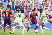 Lionel Messi (2nd right) of FC Barcelona plays the ball alongside Jordan Loties (1st right) and Alejandro Arribas (2nd left) of CA Osasuna during the La Liga match between FC Barcelona and CA Osasuna at Camp Nou on March 16, 2014 in Barcelona, Spain.