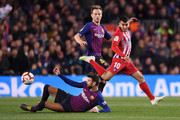 Angel Correa of Atletico Madrid battles with Gerard Pique and Ivan Rakitic of Barcelona during the La Liga match between FC Barcelona and  Club Atletico de Madrid at Camp Nou on April 06, 2019 in Barcelona, Spain.