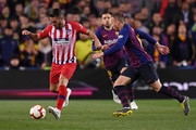 Koke of Atletico Madrid is watched by Arthur of Barcelona during the La Liga match between FC Barcelona and  Club Atletico de Madrid at Camp Nou on April 06, 2019 in Barcelona, Spain.