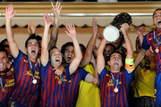 Xavi Hernandez (2nd R) of FC Barcelona holds the trophy aloft amid his teammates Alexis Sanchez (L) David Villa (2nd L), Andres Iniesta (3rd L), Cesc Fabregas (4rd L) and Daniel Alves during the UEFA Super Cup match between FC Barcelona and FC Porto at Louis II Stadium on August 26, 2011 in Monaco, Monaco.