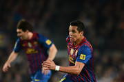 Alexis Sanchez of FC Barcelona runs with the ball backdropped by his teammate Lionel Messi during the La Liga match between FC Barcelona and Getafe CF at the Camp Nou stadium on April 10, 2012 in Barcelona, Spain.