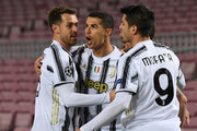 Cristiano Ronaldo of Juventus F.C. celebrates with teammates Aaron Ramsey (L) and after scoring their team's first goal  during the UEFA Champions League Group G stage match between FC Barcelona and Juventus at Camp Nou on December 08, 2020 in Barcelona, Spain. Sporting stadiums around Spain remain under strict restrictions due to the Coronavirus Pandemic as Government social distancing laws prohibit fans inside venues resulting in games being played behind closed doors.