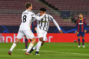 Weston McKennie of Juventus F.C. celebrates with teammate Aaron Ramsey after scoring their sides second goal during the UEFA Champions League Group G stage match between FC Barcelona and Juventus at Camp Nou on December 08, 2020 in Barcelona, Spain. Sporting stadiums around Spain remain under strict restrictions due to the Coronavirus Pandemic as Government social distancing laws prohibit fans inside venues resulting in games being played behind closed doors.