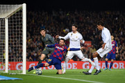 Lionel Messi of Barcelona stretches to keep the ball in play under pressure from Sergio Ramos of Real Madrid during the Liga match between FC Barcelona and Real Madrid CF at Camp Nou on December 18, 2019 in Barcelona, Spain.