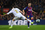Jordi Alba of Barcelona is challenged by Daniel Carvajal of Real Madrid during the Liga match between FC Barcelona and Real Madrid CF at Camp Nou on December 18, 2019 in Barcelona, Spain.