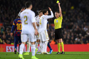Sergio Ramos of Real Madrid is shown a yellow card by Referee, Hernandez Hernandez during the Liga match between FC Barcelona and Real Madrid CF at Camp Nou on December 18, 2019 in Barcelona, Spain.