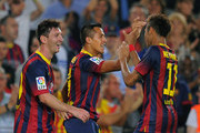 Alexis Sanchez (C) of FC Barcelona celebrates with team-mates Lionel Messi (L) and Neymar after scoring their team's second goal during the La Liga match between FC Barcelona and Real Madrid CF at Camp Nou stadium on October 26, 2013 in Barcelona, Spain.