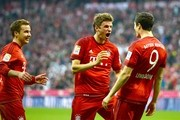 Robert Lewandowski (R) of Muenchen celebrates with Thomas Mueller (C) of Muenchen and Mario Goetze of Muenchen after scoring his team's third goal during the Bundesliga match between FC Bayern Muenchen and Borussia Dortmund at Allianz Arena on October 4, 2015 in Munich, Germany.