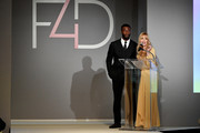 Aldis Hodge and Fashion 4 Development Founder Evie Evangelou speak onstage during Fashion 4 Development's 8th Annual Official First Ladies Luncheon at The Pierre Hotel on September 25, 2018 in New York City.
