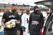 """Lorenzo """"Zo"""" Gordon and 2 Chainz deliver food packages during the Feed Your City Challenge on September 19, 2020 in Atlanta, Georgia. Feed Your City Challenge provided Atlanta's local community members with boxes of fresh groceries, PPE items, and voter registration stations."""
