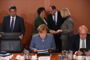 German Chancellor Angela Merkel (C) reads a document as other members of her government stand nearby at the first government cabinet meeting since the collapse of talks over a new government coalition on November 22, 2017 in Berlin, Germany. While the previous German government is still functoning as normal, the creation of a new government following federal elections last September is in limbo after the collapse of coalition talks last Sunday between the Christian Democrats (CDU/CSU), the Free Democrats (FDP) and the Greens Party (Buendnis 90/Die Gruenen). Currently the most likely course is new elections in coming months.