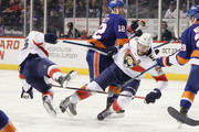 Aaron Ekblad #5 of the Florida Panthers is checked by Josh Bailey #12 of the New York Islanders during the first period at the Barclays Center on October 24, 2018 in the Brooklyn borough of New York City.