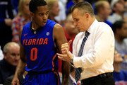 Kasey Hill #0 of the Florida Gators talks with head coach Billy Donovan on his way to the bench after coming off the floor late in the game against the Kansas Jayhawks at Allen Fieldhouse on December 5, 2014 in Lawrence, Kansas.