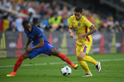 Nicolae Stanciu of Romania and Patrice Evra of France compete for the ball during the UEFA Euro 2016 Group A match between France and Romania at Stade de France on June 10, 2016 in Paris, France.