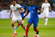 Patrice Evra of France gets past the tackle from Alan Dzagoev of Russia during the International Friendly match between France and Russia held at Stade de France on March 29, 2016 in Paris, France.