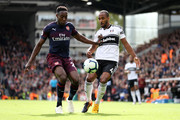 Danny Welbeck of Arsenal battles for possession with Denis Odoi of Fulham during the Premier League match between Fulham FC and Arsenal FC at Craven Cottage on October 7, 2018 in London, United Kingdom.