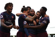 Alex Iwobi of Arsenal celebrates alongside Alexandre Lacazette of Arsenal as he celebrates with teammates after scoring his team's second goal during the Premier League match between Fulham FC and Arsenal FC at Craven Cottage on October 7, 2018 in London, United Kingdom.