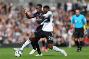 Danny Welbeck of Arsenal battles for possession with Andre-Frank Zambo Anguissa of Fulham during the Premier League match between Fulham FC and Arsenal FC at Craven Cottage on October 7, 2018 in London, United Kingdom.